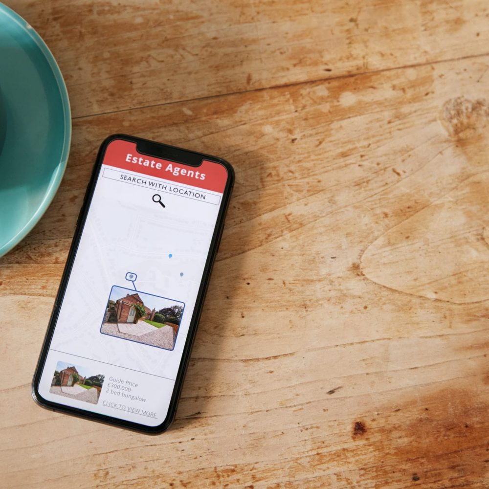 Close Up Of Mobile Phone With Realtors Property App Lying On Table
